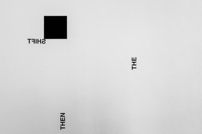SHIFT/ AND, AS, THE, THEN ; 2018 ; pièce murale avec carré noir, lettrage adhésif et peinture noire